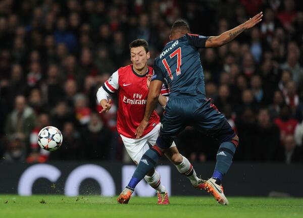 Arsenal's Mesut Ozil Challenged By Kelvin Prince Boateng During the First Leg of Their Champions League Last-16 Tie With Bayern Munich.