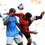 Wayne Roone and Vincent Kompany Contest for a Aerial Ball in a Premier League Match at the Etihad. Image: Getty.