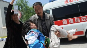 An injured woman being carried to a temporary treatment station after an earthquake in Lushan county in Ya'an in southwest China's Sichuan province Saturday, April 20, 2013.