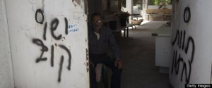 """A man sits next to anti-Christian graffiti reading in Hebrew, """"Jesus is monkey"""""""