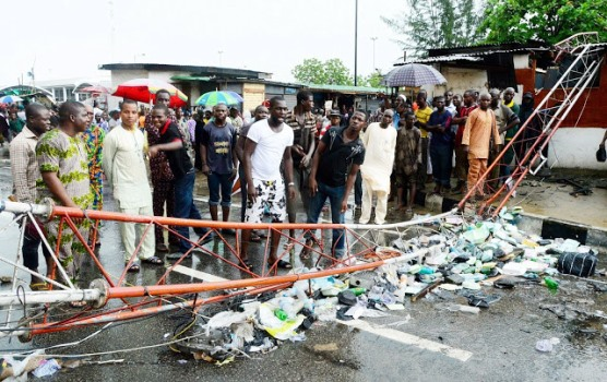 People+gathering+round+a+mast+that+collapse+on+Marina+in+Lagos,+yesterday.