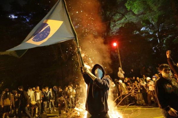 A Protester Holding the Brazilian Flag in the Middle of Tear Gas Stench.