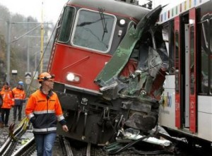 Swiss rescue personnel stand in front of a demolished RE 440 train after a train crash in the northern Swiss town of Neuhausen