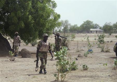 Soldiers walk through Hausari village during a military patrol near Maiduguri
