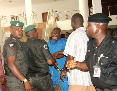 MEMBER, RIVERS  HOUSE OF ASSEMBLY, MR EVANS BAPAKAYE (M) DISCUSSING WITH  SECURITY OPERATIVES AS HE ENTERS THE ASSEMBLY CHAMBER  IN PORT HARCOURT ON TUESDAY.