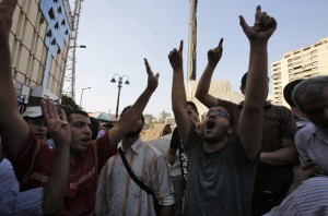 Supporters of the Muslim Brotherhood and ousted Egyptian President Mohamed Mursi shout slogans against the military and interior ministry as one gestures a 'four' during a protest in front of Al Istkama mosque at Giza Square