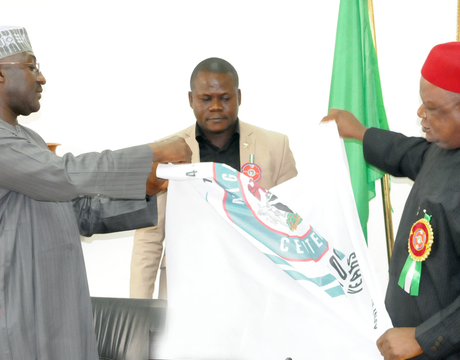 DIRECTOR-GENERAL, NATIONAL ORIENTATION AGENCY, MR MIKE OMERI (L), PRESENTING THE  COMMEMORATIVE NIGERIAN CENTENARY CELEBRATION FLAG TO THE SECRETARY TO THE GOVERNMENT OF THE FEDERATION, SEN. ANYIM PIUS ANYIM, IN ABUJA ON FRIDAY (20/12/13).