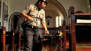 A policeman with a bomb sniffing dog inspects a church in the East Java city of Surabaya in September, 2011, following a suicide bomber attack targeting Christians in the Central Java city of Solo.  AFP photo