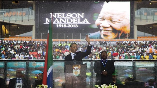 PRESIDENT BARACK OBAMA WAVES AS HE ARRIVES TO SPEAK TO CROWDS ATTENDING THE MEMORIAL SERVICE FOR FORMER SOUTH AFRICAN PRESIDENT NELSON MANDELA AT THE FNB STADIUM IN SOWETO NEAR JOHANNESBURG, TUESDAY, DEC. 10, 2013. (AP PHOTO/EVAN VUCCI)