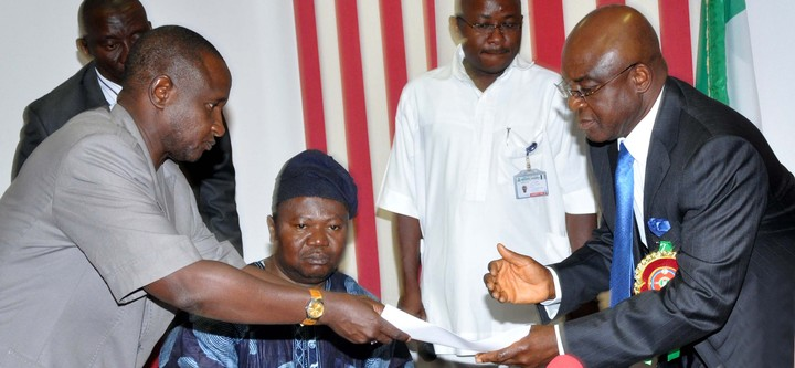 PRESIDENT OF ASUU, DR ISA FAGGE (L), PRESENTING SIGNED AGREEMENT BETWEEN ASUU AND FG TO THE SENATE PRESIDENT DAVID MARK, DURING ASUU LEADERSHIP VISIT TO THE SENATE  IN ABUJA ON THURSDAY (19/12/13). WITH THEM IS ASUU VICE PRESIDENT, PROF. BIODUN OGUNYEMI (NAN).