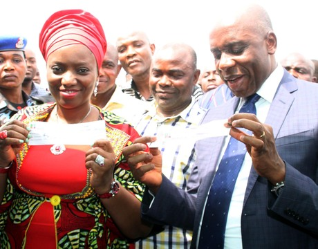 WIFE OF THE GOVERNOR OF RIVERS, MRS JUDITH AMAECHI (L) AND GOV. CHIBUIKE AMAECHI, DISPLAYING THEIR REGISTRATION SLIPS AS MEMBERS OF THE ALL PROGRESSIVES CONGRESS (APC) AT UBIMA IN RIVERS ON MONDAY (10/2/14).