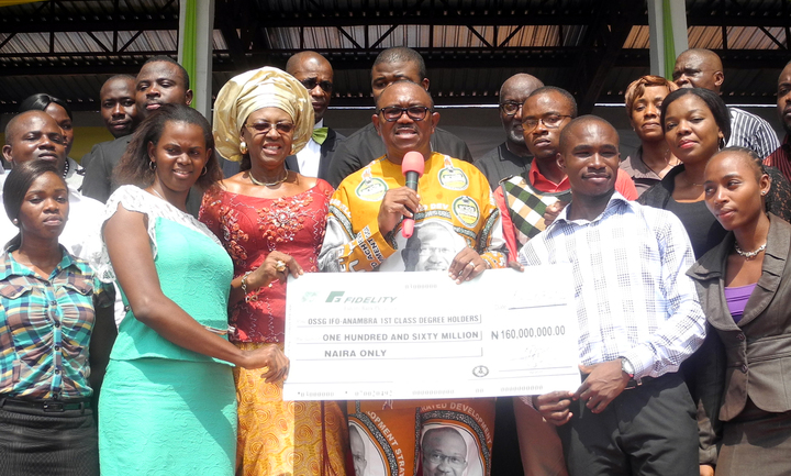 GOV. PETER OBI OF ANAMBRA (M), PRESENTING A DUMMY CHEQUE OF N160 MILLION TO SOME OF THE 160 FIRST CLASS GRADUATES OF THE STATE TO ENABLE THEM ESTABLISH THEMSELVES IN THEIR CHOSEN CAREERS IN AWKA ON THURSDAY (13/3/14).